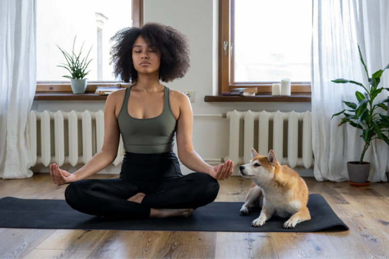 women on yoga mat mediating with dog